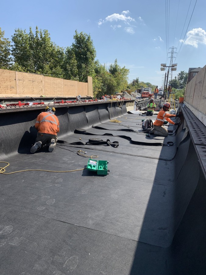 Crews work on black ballast mats.