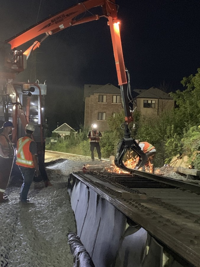 Work crews install new ties at night.
