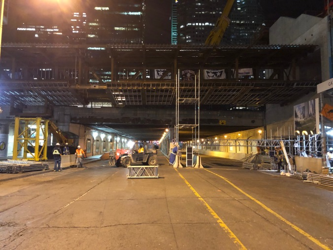 Workers toil under the bridge being put in place over Bay Street.