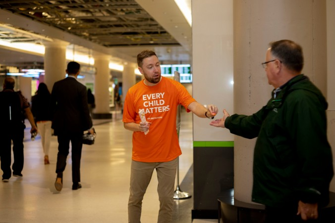 A volunteer hands out a Orange Shirt Day sticker.