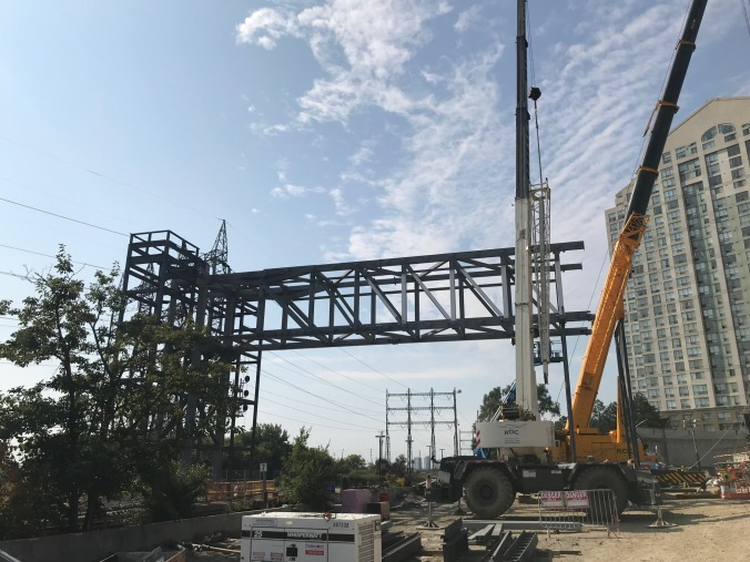 A large metal skeleton structure of a bridge is lifted with a big crane