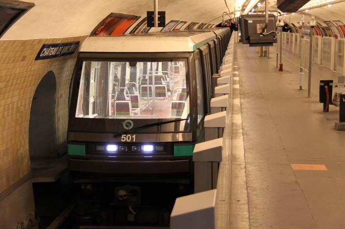 A Paris subway train sits at the platform.