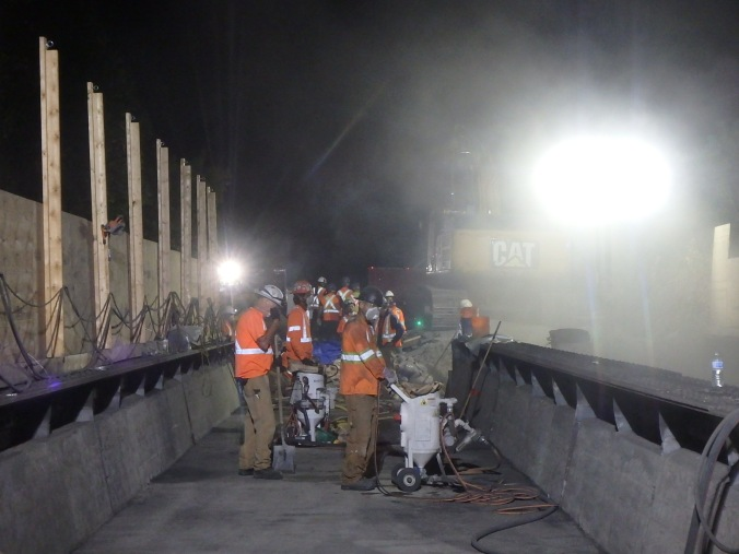 A night shot shows workmen sand blasting concrete on a bridge.