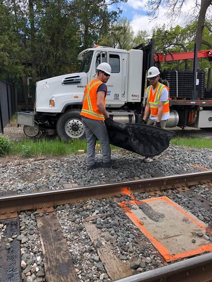 workers carry an anti-trespass mat from a truck to the train tracks.