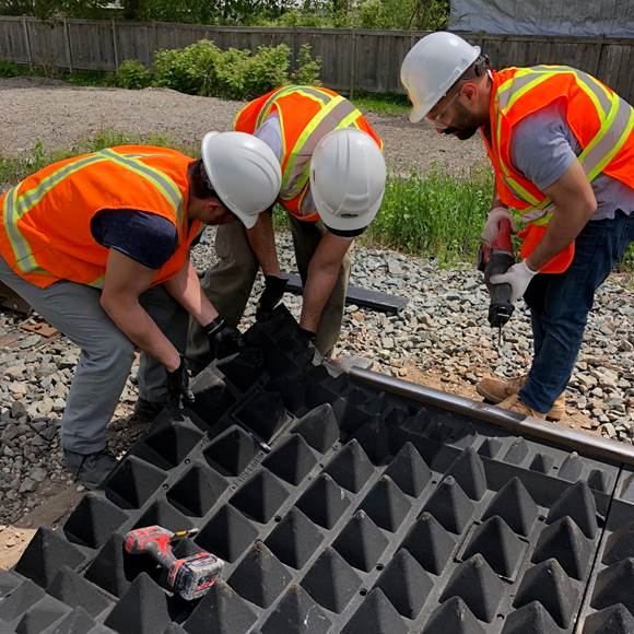 Crews work on installing mats next to the tracks