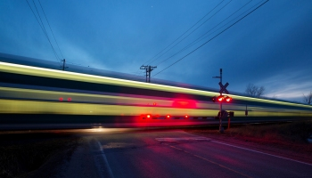 A GO train makes its way through a crossing at high speed.