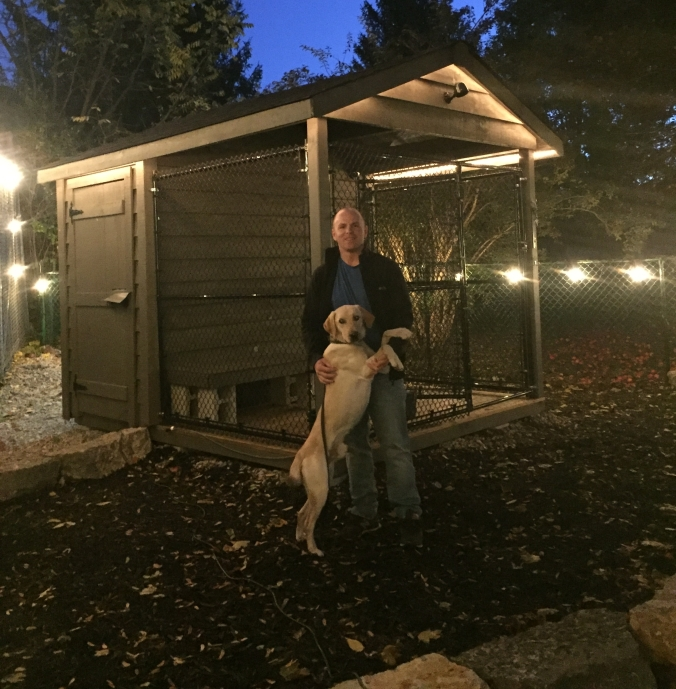 Officer Hoffman hugs Dash, as they stand beside his outdoor kennel.