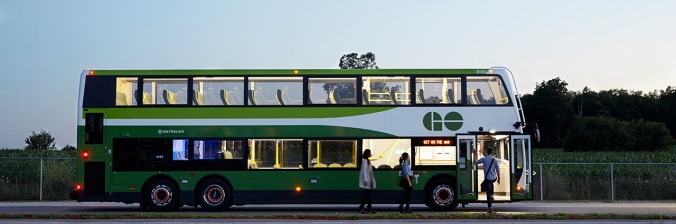 A GO bus is lit up. as customers board.