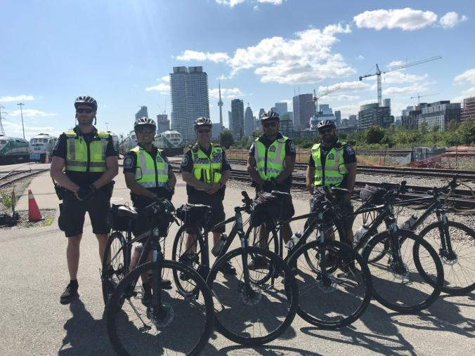 Officers pose in front of GO trains.