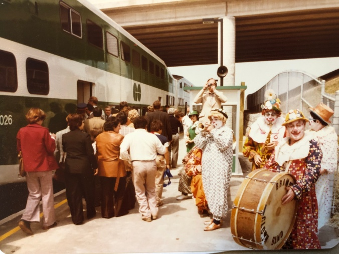 A clown band plays as customers board a GO train.