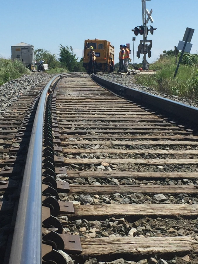 A line of rail is seen, lesading to crews working at an intersection.