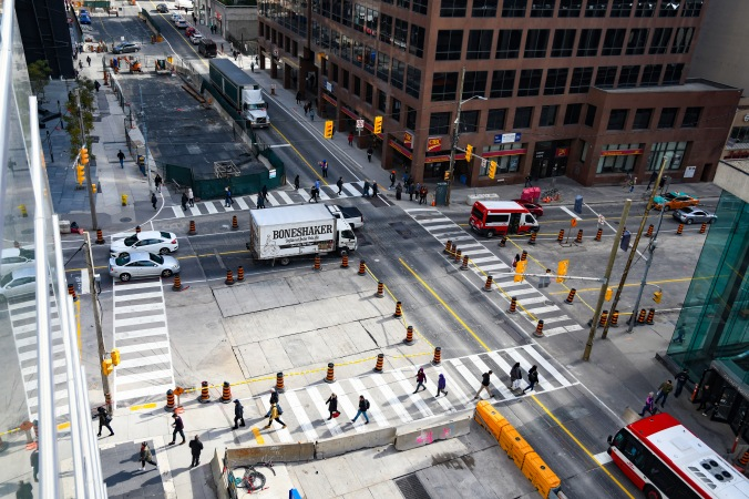 Shot from above, pedestrians walk around the crosswalks at the important intersection.