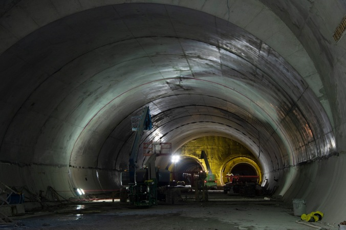 The tunnel is shown in concrete, as a cherry-picker crane reaches for the ceiling.