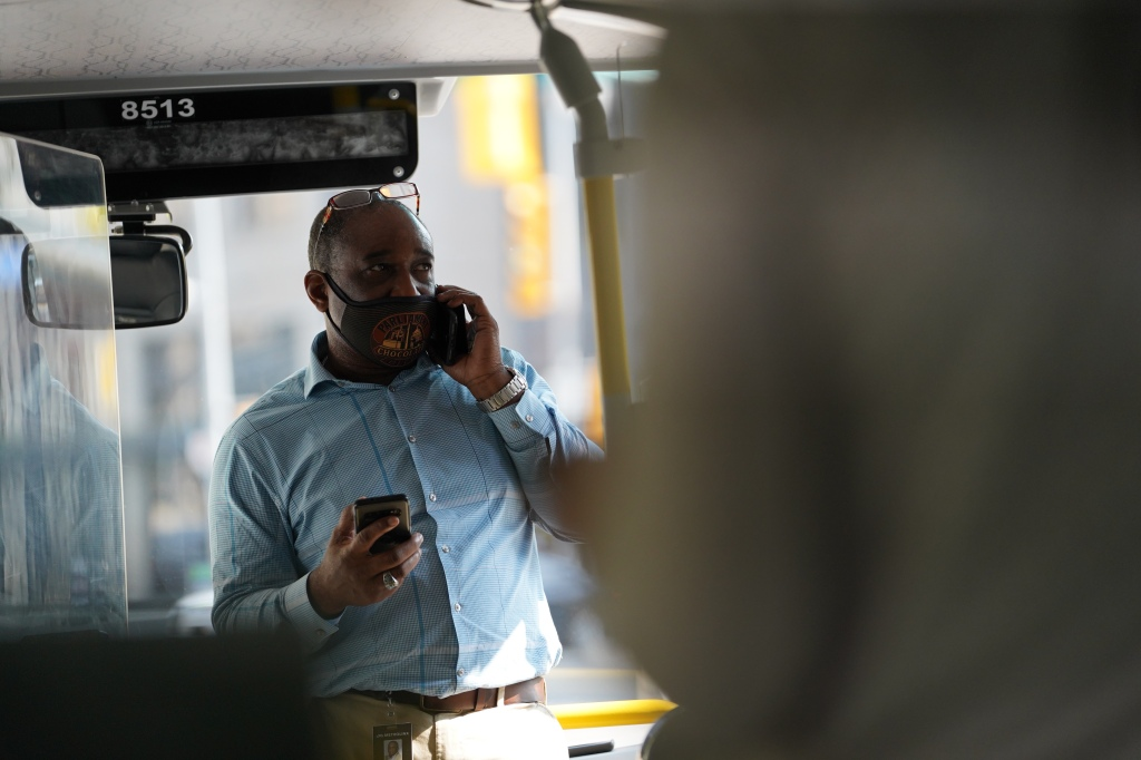 A man uses a phone on a GO bus.
