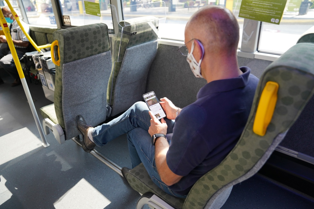 A man sits on a GO bus and looks at his phone.