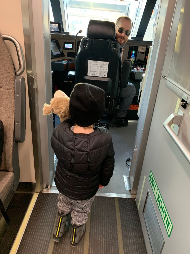 A child stands before a conductor on a train.