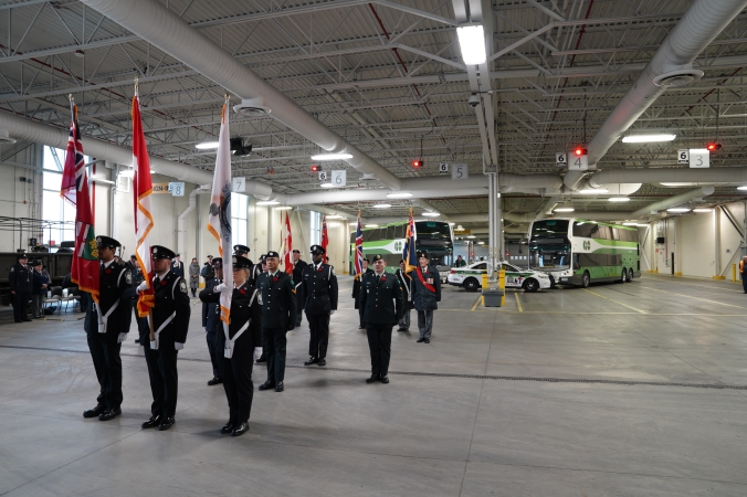 An honour guard walks past a reviewing stand, as they carry flags.
