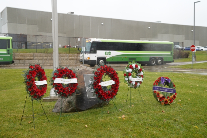 A GO bus drives past a military marker and wreaths.
