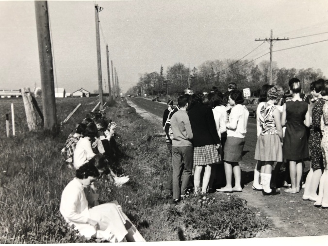Teens gather on a roadway.