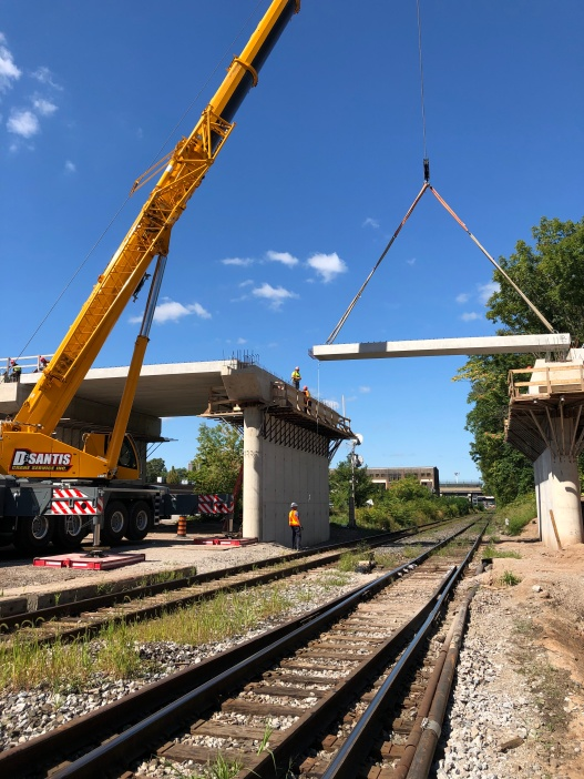 A large piece of concrete is lowered into place as part of a bridge replacement over top of train tracks.