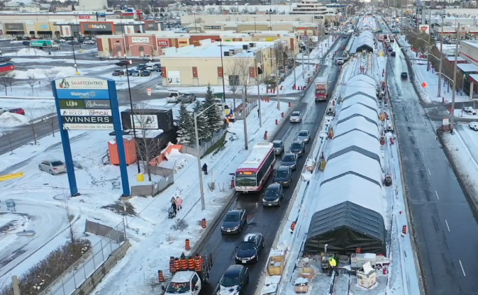 In a still from a video, the image looks down on large tents built over the Crosstown rail line.
