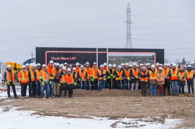 A large group pose for the camera, after breaking ground.