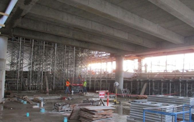 Workers work inside the concrete shell of the station.