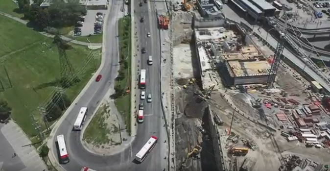 Image is shot from above, and shows the construction area, with buses moving nearby.