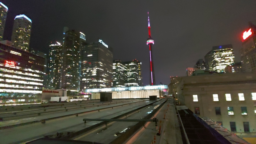 View of the trainshed at Union Station with the glowing CN Tower in the background.