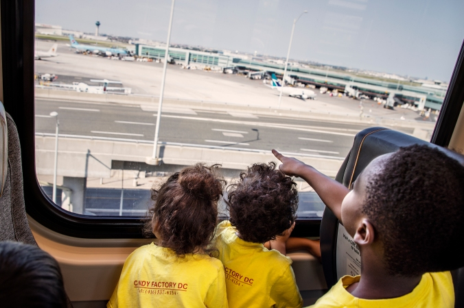Children stare out the window toward the airport, and planes moving about.