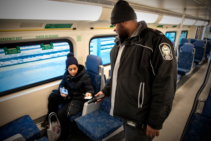 An officer checks a PRESTO card, held out by a customer.