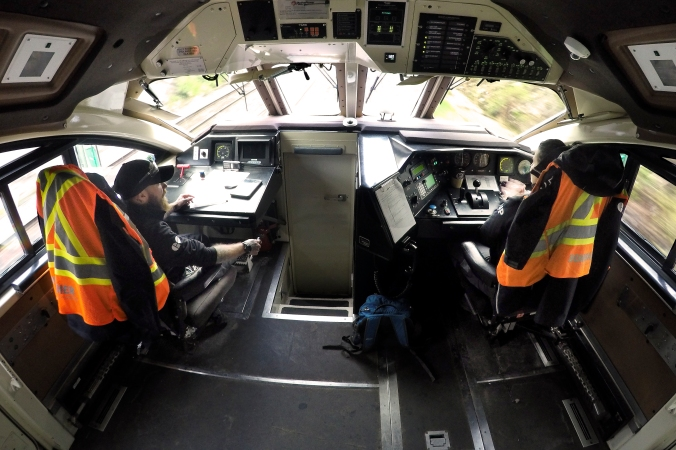 An inside view of the GO locomotive cab with two operators sitting in the chairs.