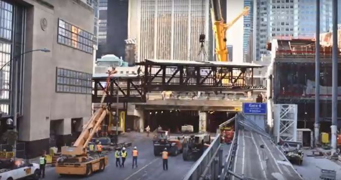 Image shows workers lifting the span into place.