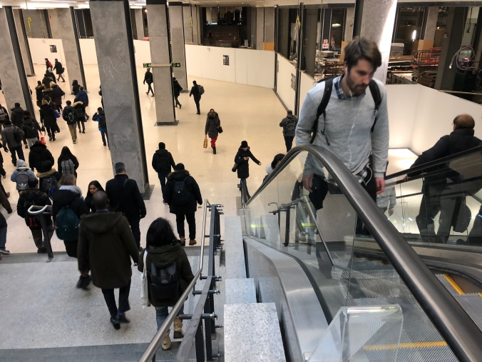 Travellers go down the stairs and up the escalators.