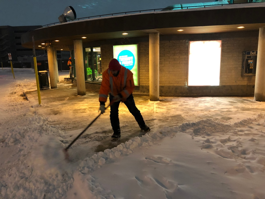 A man moves snow on a walkway in the early morning.
