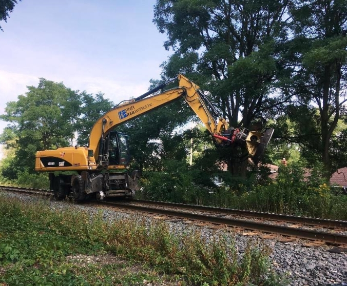 Image of a large tree removing machine working on a rail line.
