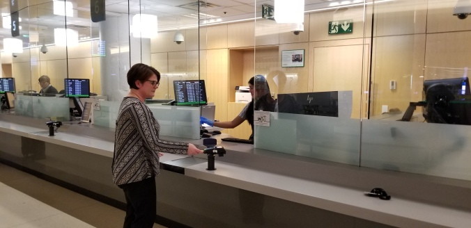 A ticket agent interacts with a customer from behind glass.