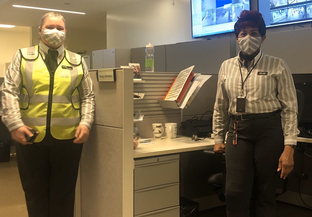 Image shows two staff members with face coverings made out of the same material as their uniforms.