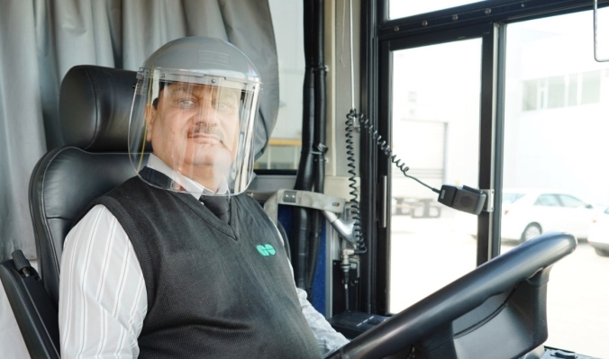 A bus driver wears a face shield.