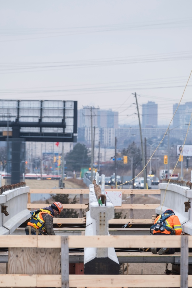 Two workmen work next to large girders on a cold day.