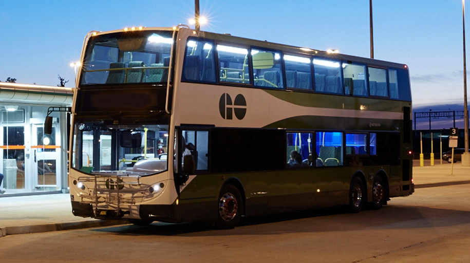 A GO bus waits at a platform in the early morning.