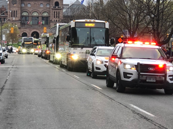 A line of emergency vehicles moves through downtown Toronto.
