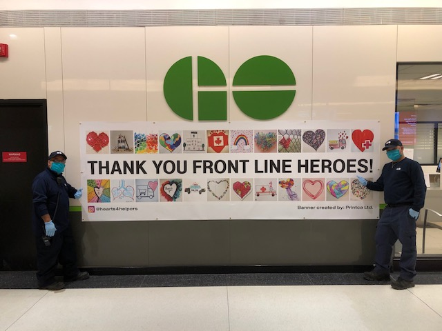 Two staff members display the large 'Thank you front line heroes' banner.