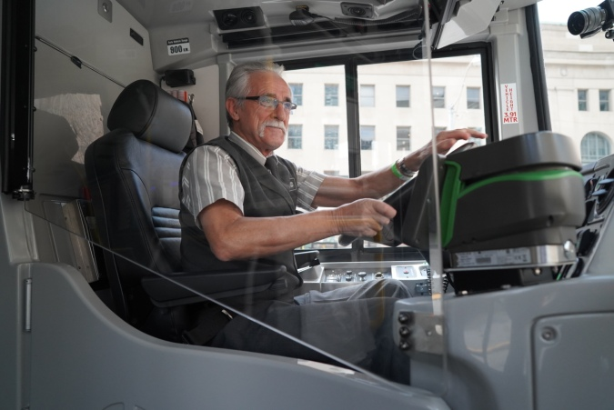 Image shows a bus driver with hands on the wheel, circled by a clear barrier.