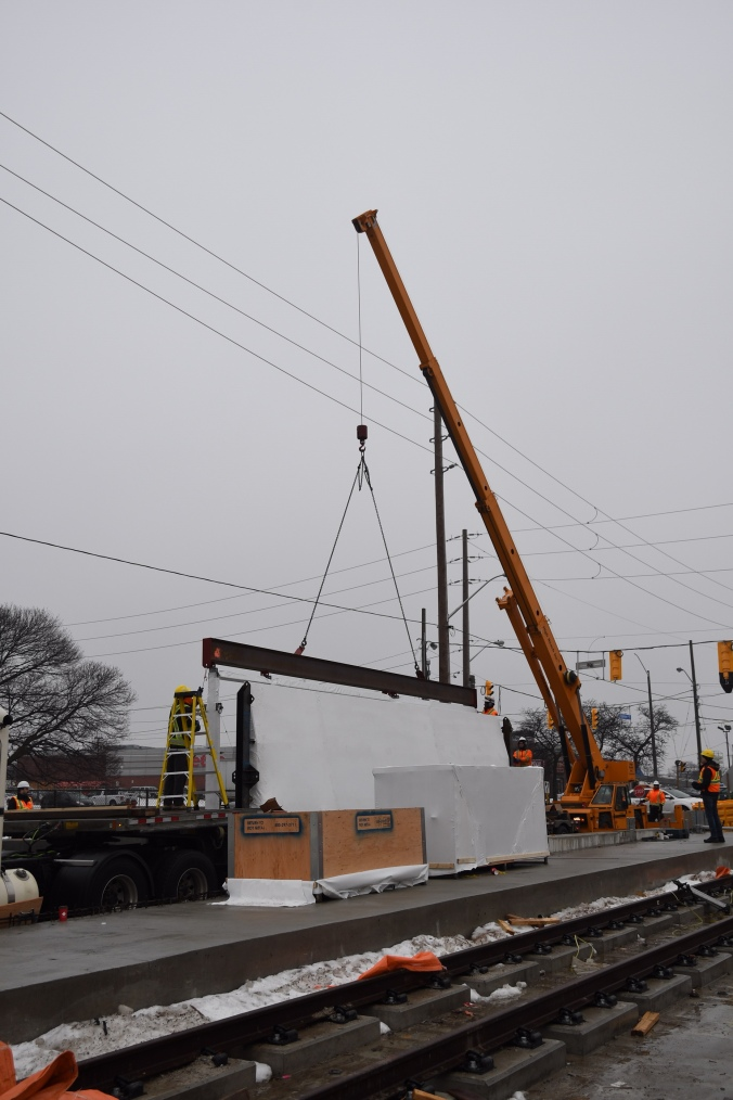 Image shows a crane moving a shelter into place.