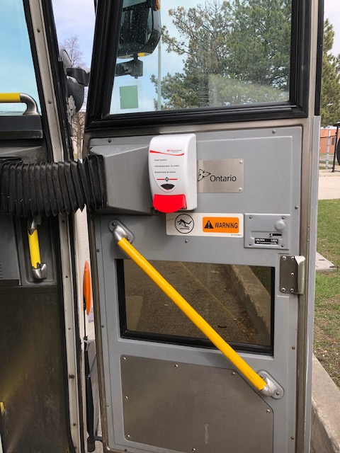 Image is a hand sanitizer machine attached to a bus door.