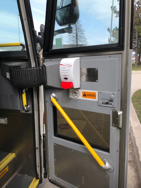 A dispenser is shown attached to a bus door.