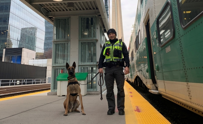 Image shows oficer Ng holding the leash of Tango, who sits on an outside platform.