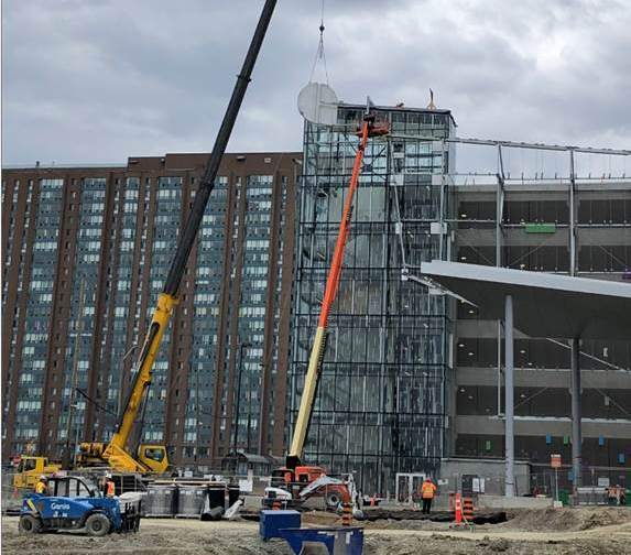 A specialized crane lifts the 'G' that will spell GO into place on the parking garage at Cooksville GO Station