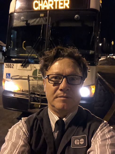 An image of a bus driver in front of a bus.